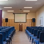 blue chairs in a function room with screen and lecturn at the front