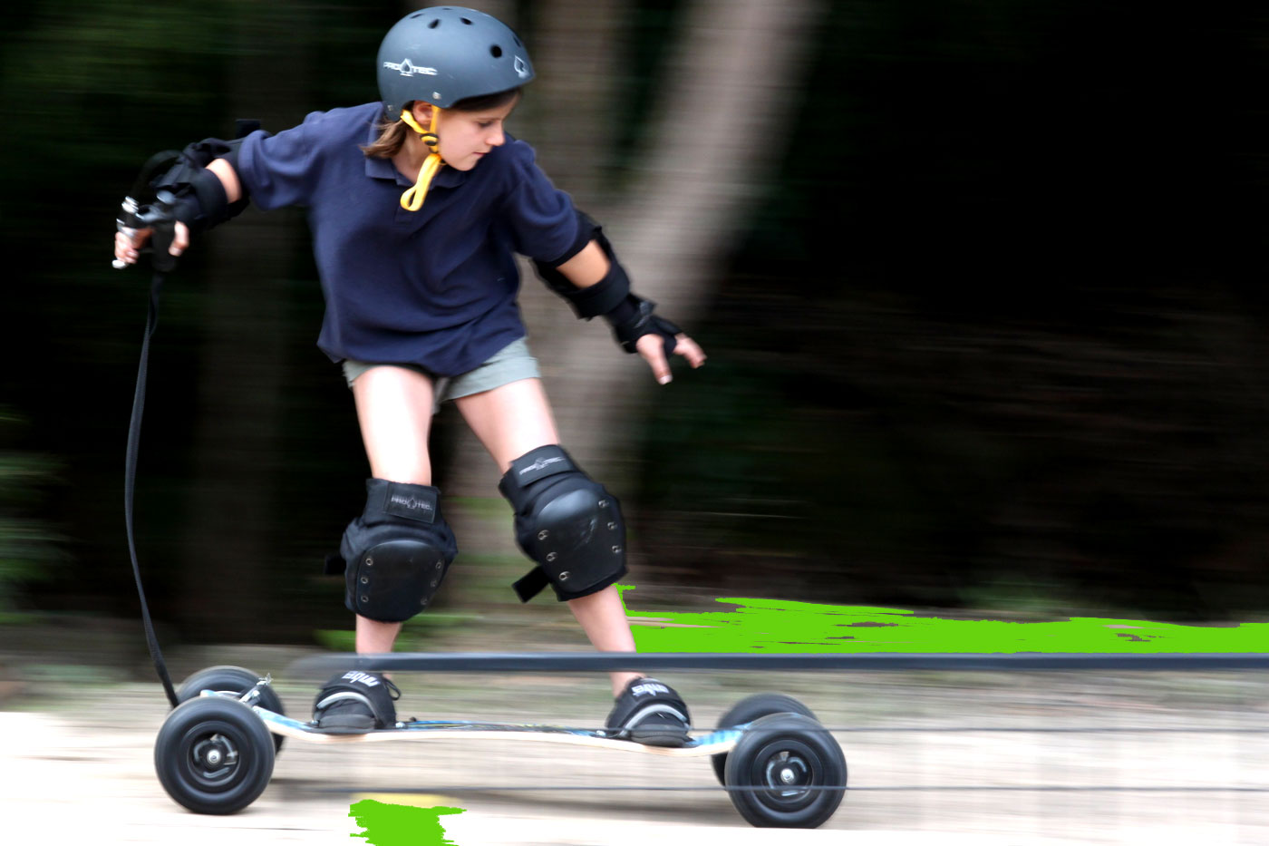 Picture of a kid at speed, on a mountain board